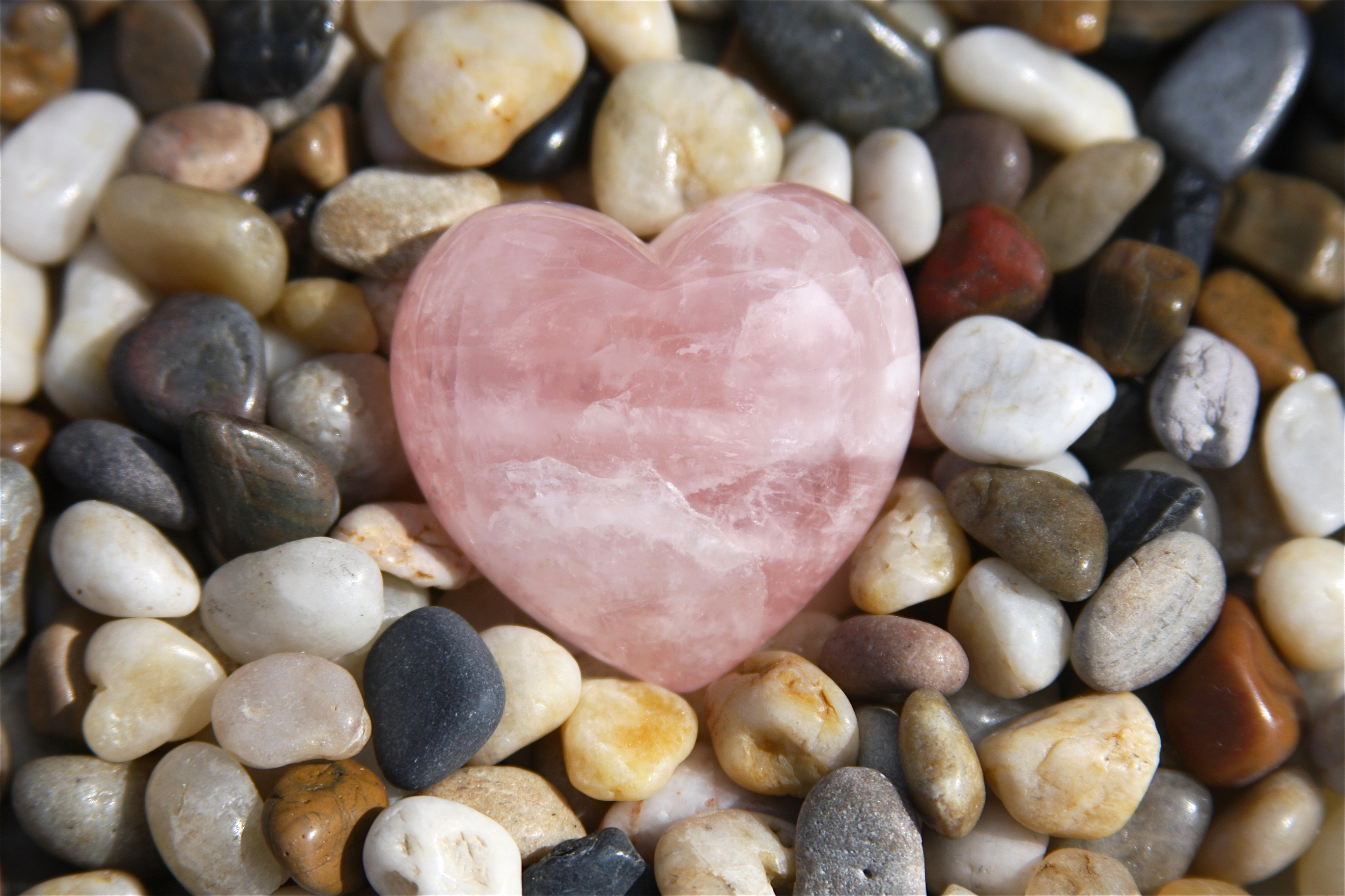 Rose quartz heart on stones