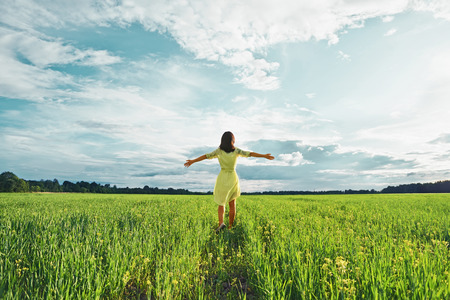 32823478 - young woman with her arms wide spread is enjoying in the sunny summer day