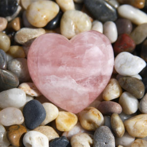 Rose quartz heart on stones